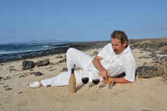 Happy man on the beach has two glasses of red wine Stock Photo