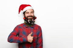 Happy man with beard and christmas decorations showing thumb up. Portrait of happy man with beard with christmas decorations and santa helper hat showing thumbs Stock Photography