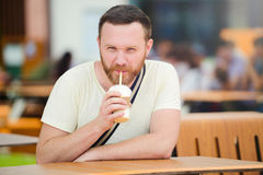 Happy man with a beard drinking a soft drink in the city smiling, cold coffee. stock photos