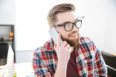 Happy man with beard in glasses talking on cell phone Royalty Free Stock Images