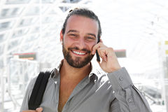 Happy man with beard talking on mobile phone at station Stock Photo