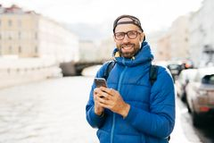 Happy man with beard wearing eyeglasses dressed in blue anorak holding backpack and mobile having happy look travelling in city wa. Tching sightseeings and royalty free stock photo