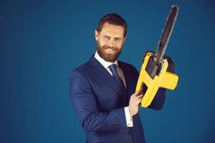 Happy man or bearded businessman hold yellow chainsaw in outfit. Happy man or bearded businessman hold yellow chainsaw in formal outfit on blue background, copy royalty free stock image