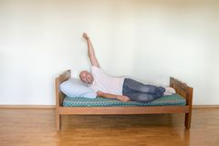 A happy man on a bed in an empty room. The concept of asceticism makes a person happy.  royalty free stock photos