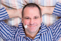 Happy man in the bed. Happy man resting on his back in the bed Royalty Free Stock Photos