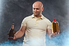 Happy man with a beer. Happy man with lots of beer in confusion on a black background royalty free stock images