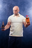 Happy man with a beer. Happy man with lots of beer in confusion on a black background stock photography