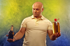 Happy man with a beer. Happy man with lots of beer in confusion on a colored background stock image