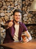Happy man with beer showing thumbs up at bar Stock Photos