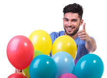 Happy man behind a baloons bunch making ok. Happy man behind a baloons bunch is making the ok thumbs up sign on white background stock photo