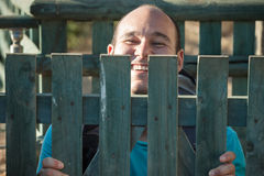 Happy man behind fence Stock Image
