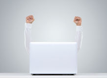 Happy man behind the laptop. Happy successful businessman rising arms up behind the desk Royalty Free Stock Images