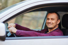Happy man behind the wheel of a new car Stock Photos