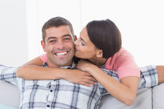 Happy man being kissed by woman Stock Images