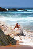 Happy man being splashed by a wave on the beach Stock Photo