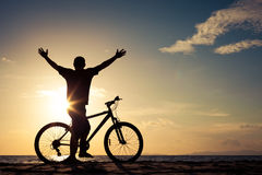 Happy man with bicycle standing on the beach Royalty Free Stock Image