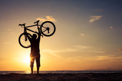 Happy man with bicycle standing on the beach Stock Photo