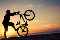 Happy man with bicycle standing on the beach Stock Photography