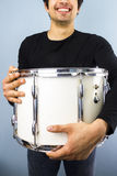 Happy man with big drum. Young man smiling and holding a big drum Stock Photography