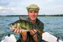 Happy man with big perch fishing trophy Stock Photos