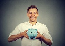 Happy man with blue piggy bank stock images