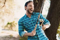 A happy man in a blue shirt stands on the river bank and holds a spinning in his right hand, twisting reel by left. A man in a blue shirt posing with a spinning Royalty Free Stock Photography