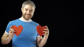 Happy man in blue tshirt holds two red heart shapes. Love, romance, dating, relationship concepts. Black background. 4K. Shot stock video