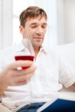 Happy man with book and glass of red wine at home Stock Photos