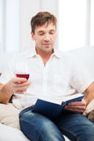 Happy man with book and glass of rose wine at home Stock Photography