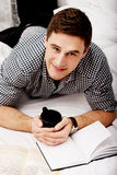 Happy man with a book in his bed. Royalty Free Stock Photos