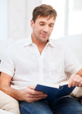 Happy man with book at home Royalty Free Stock Image