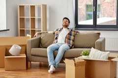 Happy man with boxes sitting on sofa at new home. Moving, people and real estate concept - happy man with boxes sitting on sofa at new home stock image