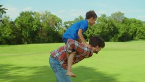 Man and boy playing in meadow. Father giving son piggyback riding outdoors