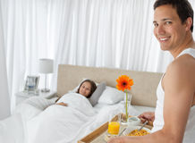 Happy man bringing the breakfast on the bed royalty free stock images