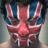 Happy man with British flag on face looking down Royalty Free Stock Photos