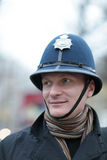 Happy man in british police hat. The happy man posing in british police hat Royalty Free Stock Image