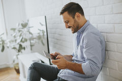 Happy man browsing in a tablet sitting on commode at home Stock Photos
