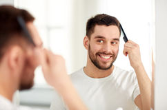 Happy man brushing hair with comb at bathroom. Beauty, grooming and people concept - smiling young man looking to mirror and brushing hair with comb at home royalty free stock images