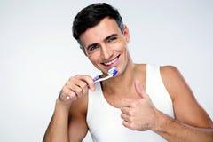 Happy man brushing his teeth Stock Photos