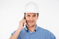 Happy man building engineer in helmet talking on mobile phone Royalty Free Stock Image