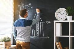 Happy man businessman, student writes on blackboard stock image