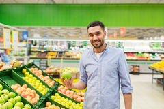 Happy man buying green apples at grocery store. Shopping, food, sale, consumerism and people concept - happy man buying green apples at grocery store or stock photos