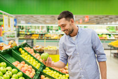 Happy man buying green apples at grocery store. Shopping, food, sale, consumerism and people concept - happy man buying green apples at grocery store or royalty free stock image