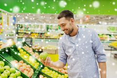 Happy man buying green apples at grocery store. Shopping, food sale, consumerism and people concept - happy man buying green apples at grocery store or royalty free stock photography
