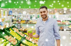Happy man buying green apples at grocery store Stock Image