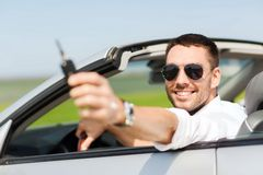 Happy man in cabriolet showing car key. Auto business, transport, leisure and people concept - happy man in cabriolet showing car key Stock Photos
