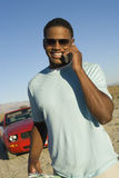 Happy Man On A Call. Portrait of happy African American man on a call with car in background stock images