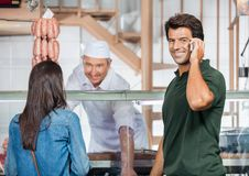 Happy Man On Call While Woman Buying Meat Royalty Free Stock Photo