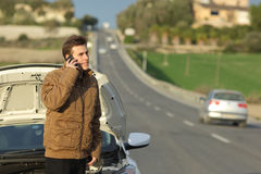 Happy man calling roadside assistance for his breakdown car Royalty Free Stock Image
