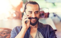 Happy man calling on smartphone at bar or pub. People, communication and technology concept - happy man calling on smartphone at bar or pub Royalty Free Stock Photos